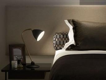 detalhe de roupa de cama e luminária em quarto